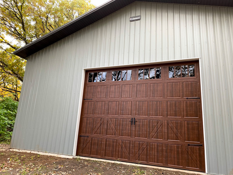 Amarr Classica 3000 in Walnut with Lucern Panels and Thames Windows.  Installed by Augusta Garage Door in Clearwater, MN.